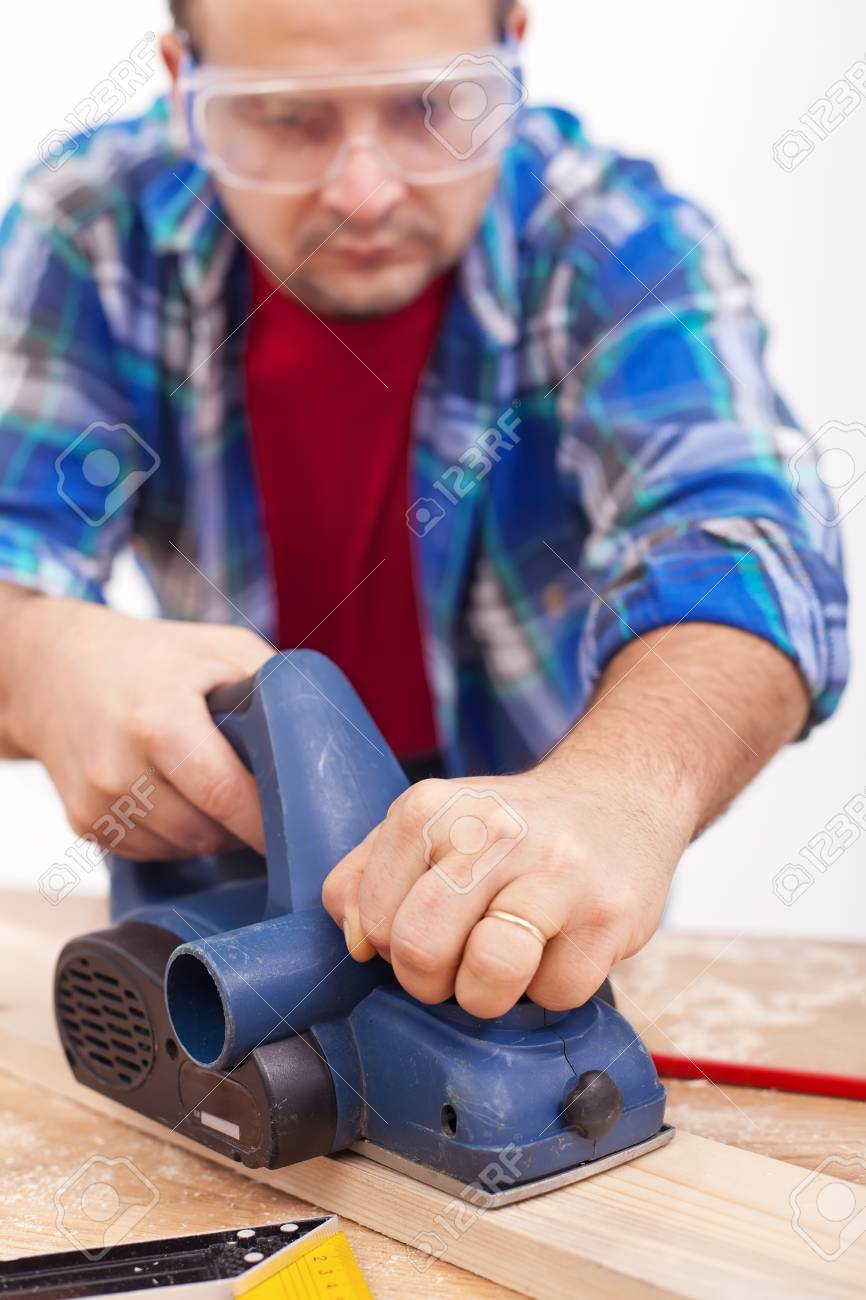 Man working with wooden planck and electric planer - closeup Stock Photo - 12375580