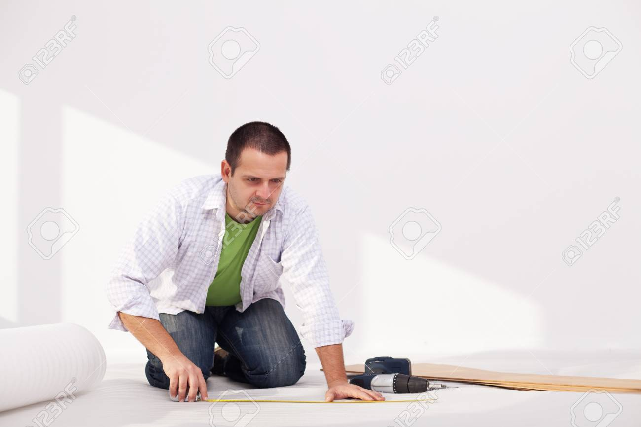 Man laying flooring at home - the isolation layer Stock Photo - 13612545
