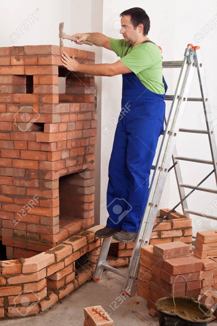 Worker building masonry heater - finishing the firebox with chamotte bricks Stock Photo - 16585085