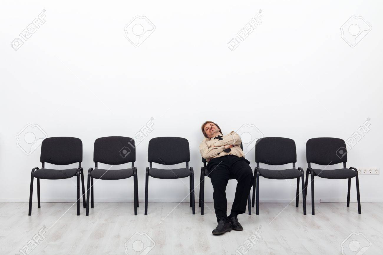 Tired businessman waiting - sitting on a chairs row - 17370158