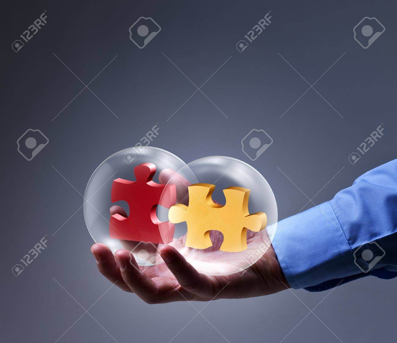 Businessman presenting a brand new solution - two puzzle pieces in glass spheres Stock Photo - 17931663