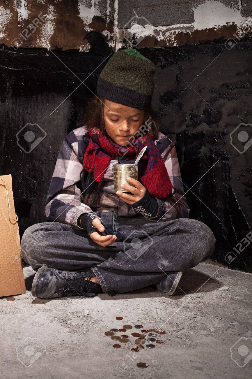 Beggar child boy reviews the money he received looking into tin can - 19989802
