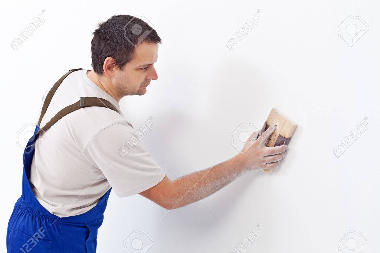 Worker scrubbing the wall with sandpaper - preparing the surface for painting - 22247598