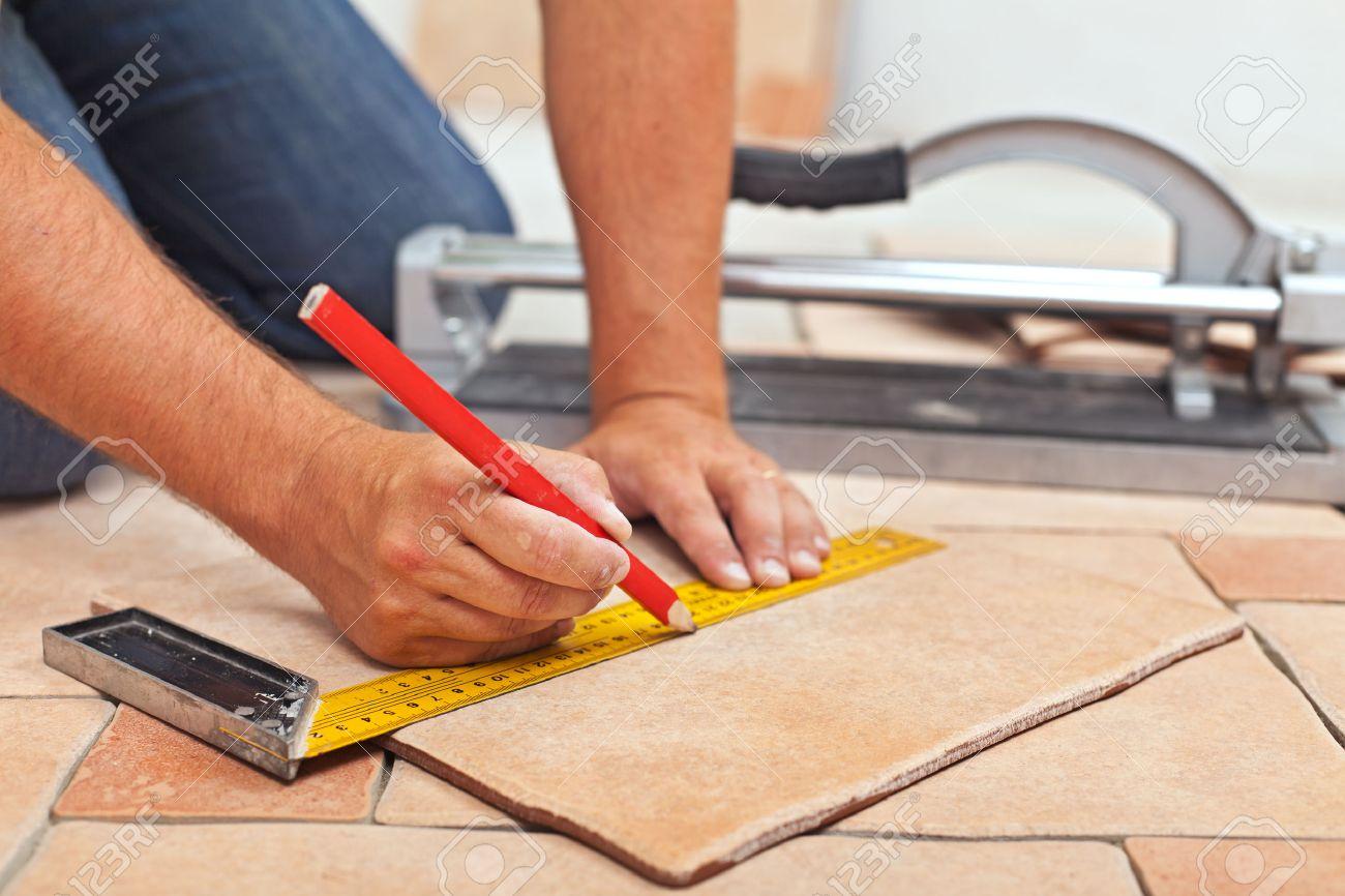Laying ceramic floor tiles - man hands marking tile to be cut, closeup - 23447633