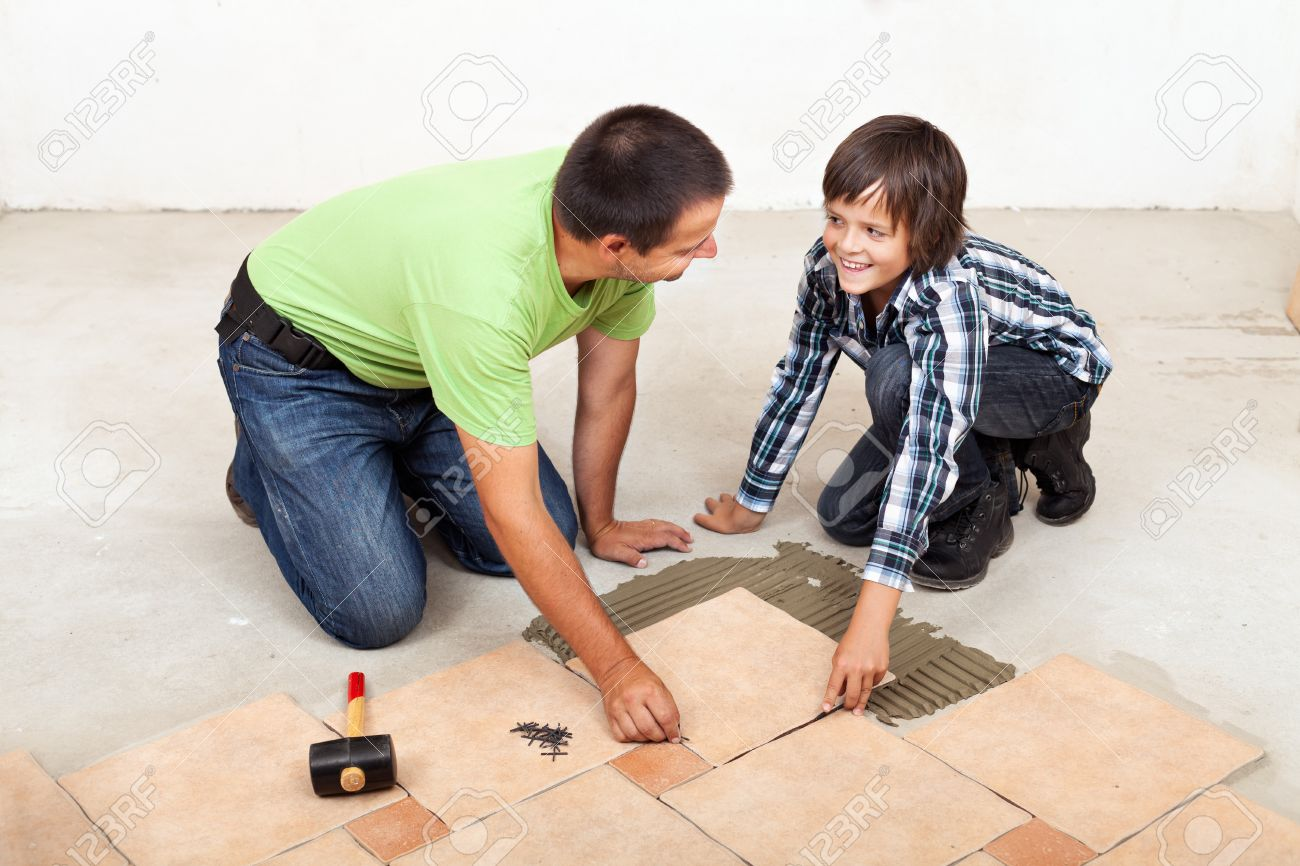Smiling Father And Son Laying Ceramic Floor Tiles Together Stock Photo    22247607
