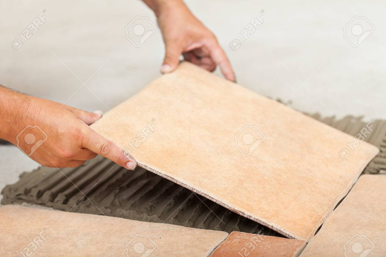 Laying ceramic floor tiles man hands fitting the next piece laying ceramic floor tiles man hands fitting the next piece closeup stock photo dailygadgetfo Images