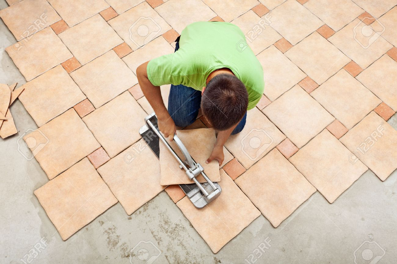 Man laying ceramic floor tiles working with a cutter device - top view - 22247609