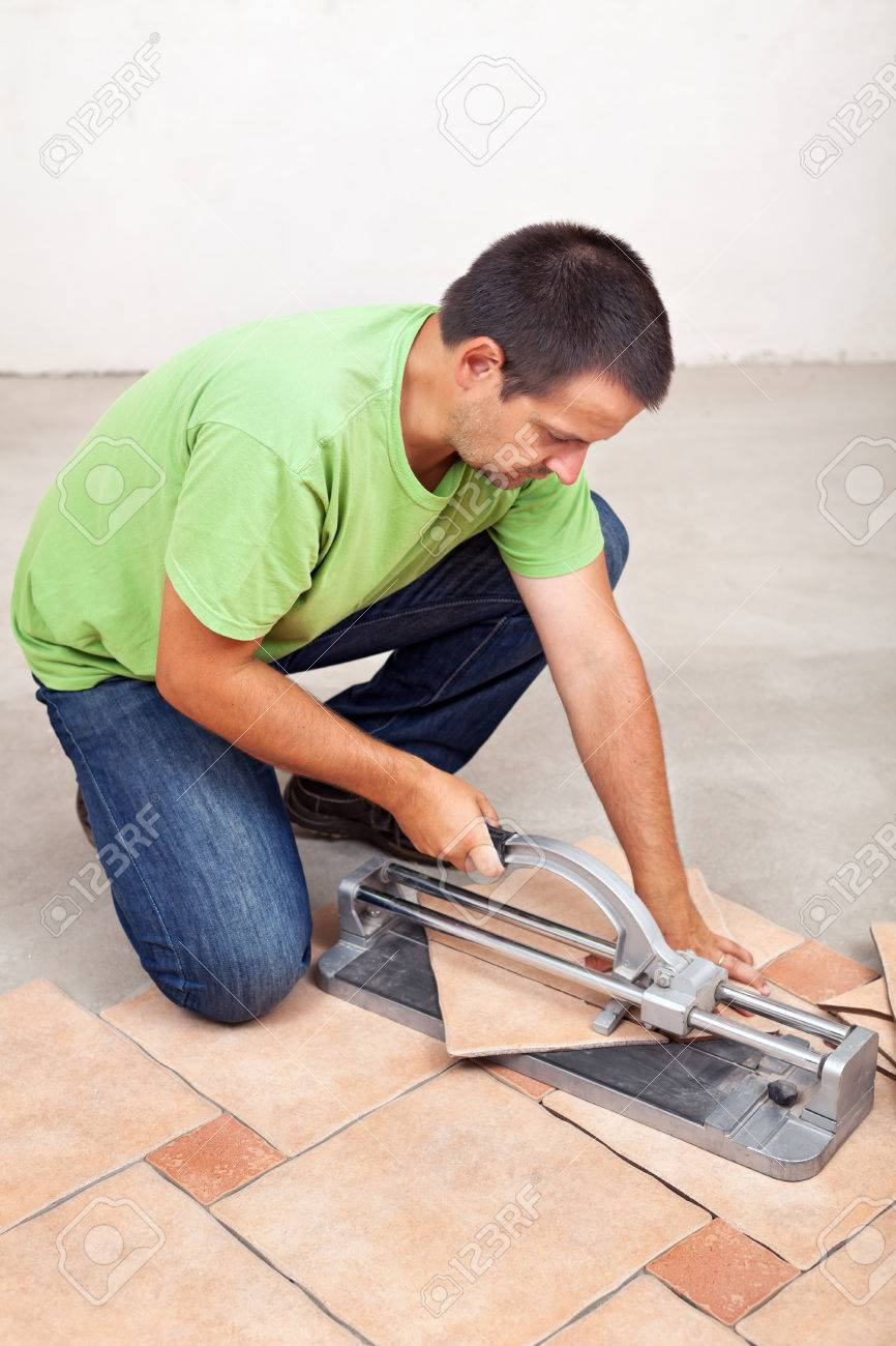 Man cutting floor tiles with manual cutter device stock photo man cutting floor tiles with manual cutter device stock photo 22247614 dailygadgetfo Gallery