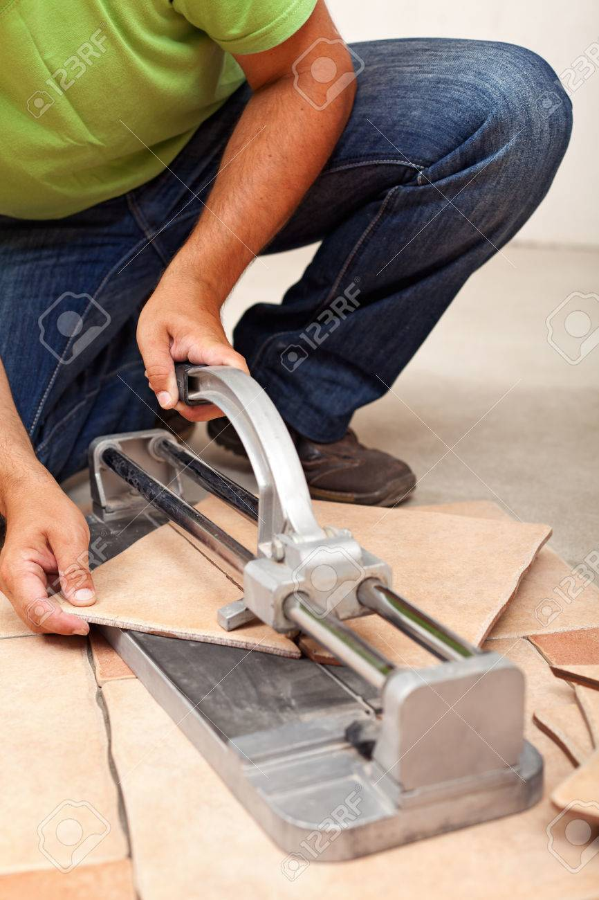 Worker Cutting Ceramic Floor Tiles Closeup On Cutter And Hands