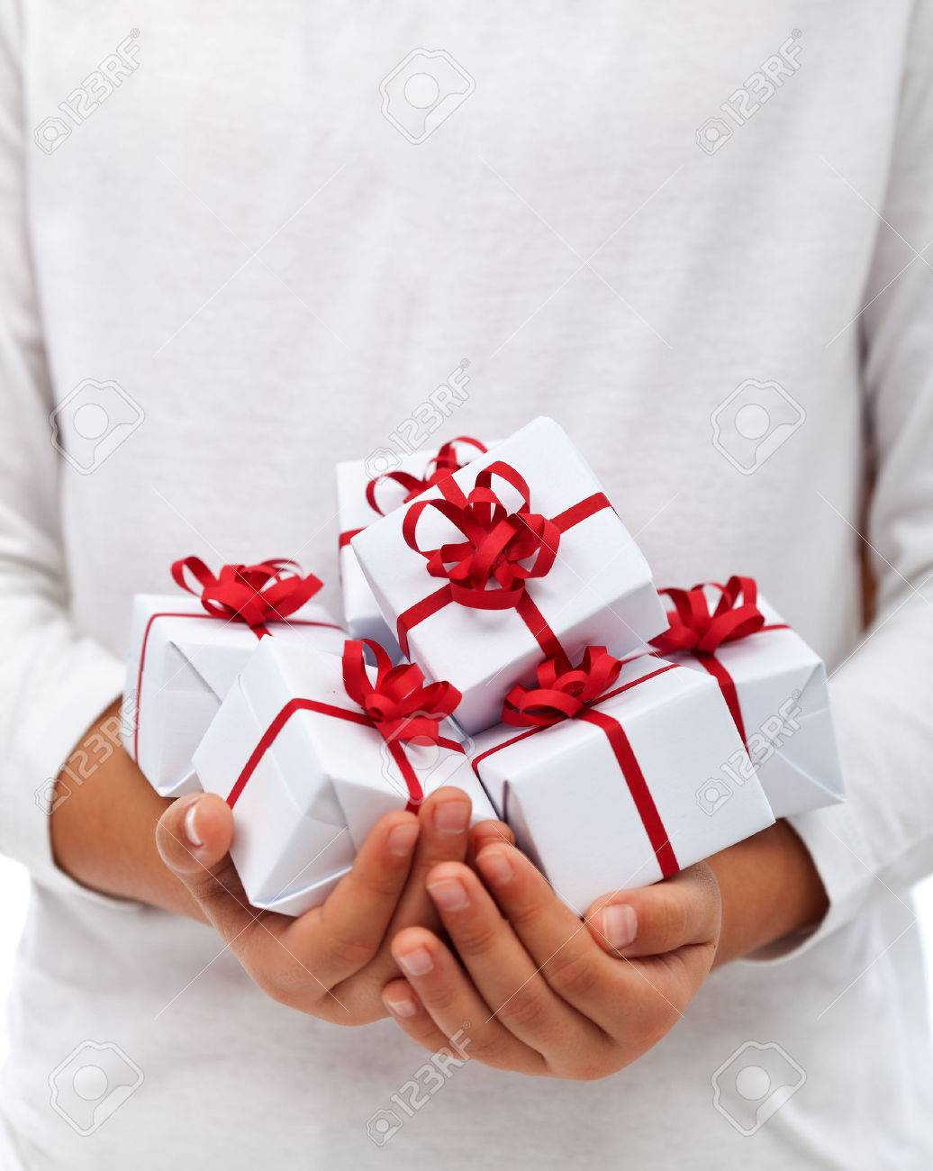 Lots of christmas presents in child hands - thankfulness for abundance concept, with copy space - 23999731