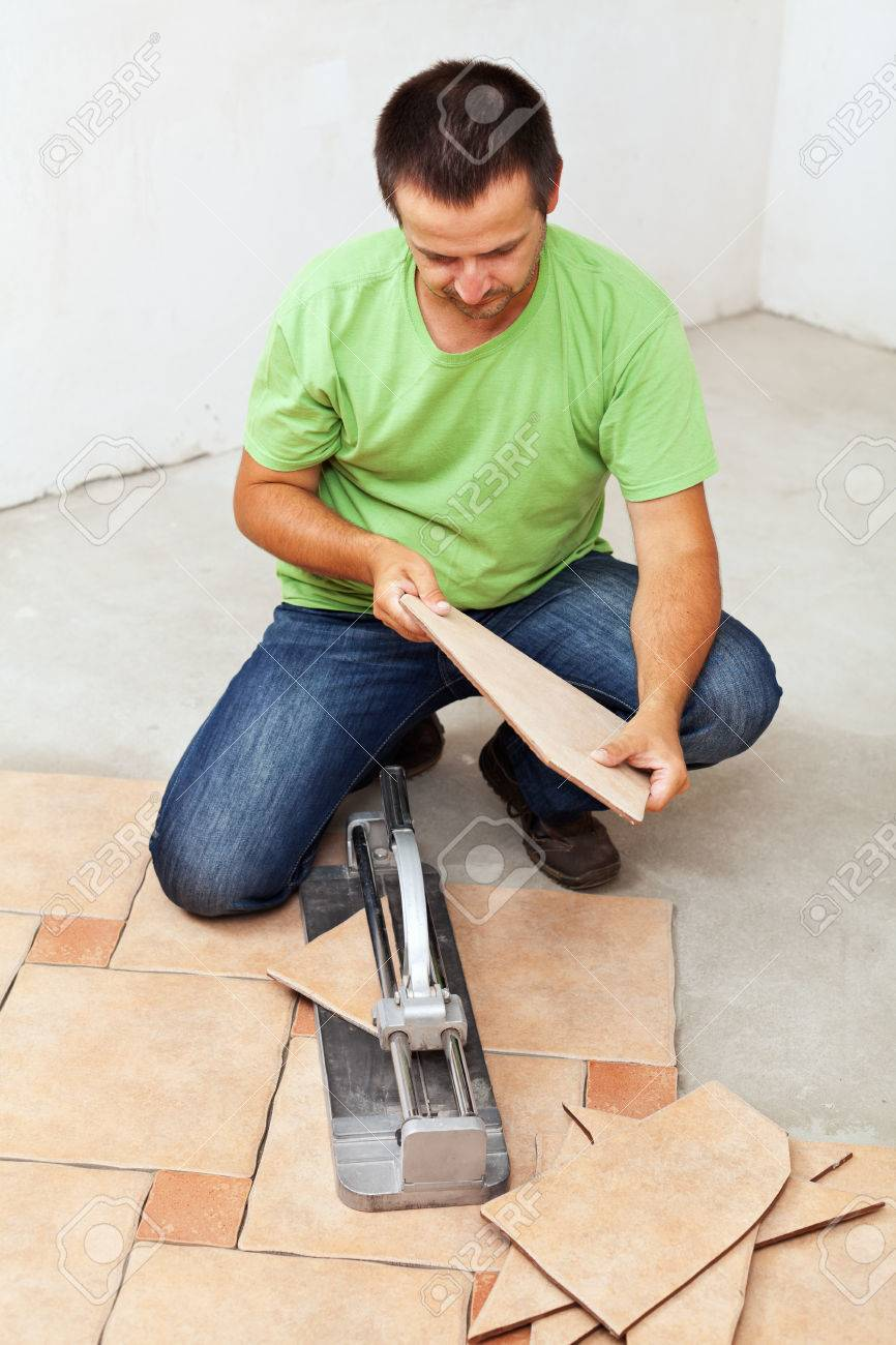 Worker cutting and installing ceramic floor tiles stock photo stock photo worker cutting and installing ceramic floor tiles dailygadgetfo Gallery