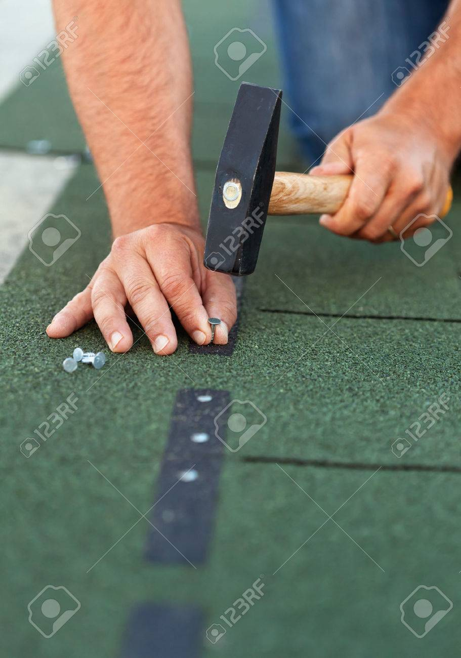 Worker installs bitumen roof shingles - closeup on hands with nails and hammer - 25754272