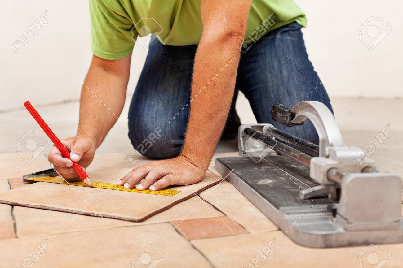 Worker hands laying ceramic floor tiles - measuring and marking one piece - 26049742
