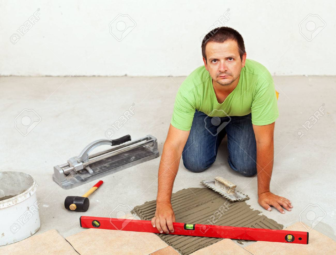 Man laying ceramic floor tiles on concrete floor checking his man laying ceramic floor tiles on concrete floor checking his work with a spirit level dailygadgetfo Image collections