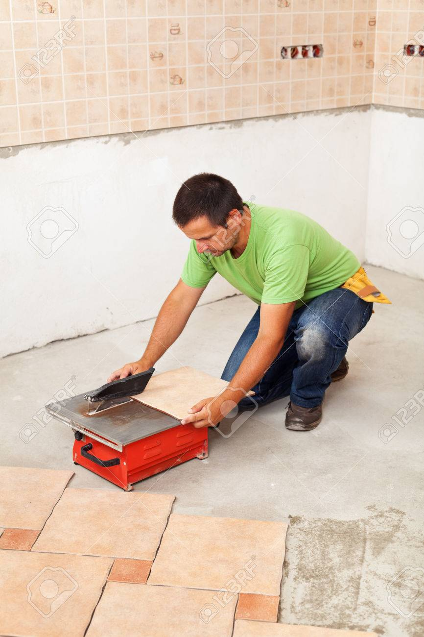 Man Cutting Ceramic Floor Tiles - Laying Them On The Concrete ...