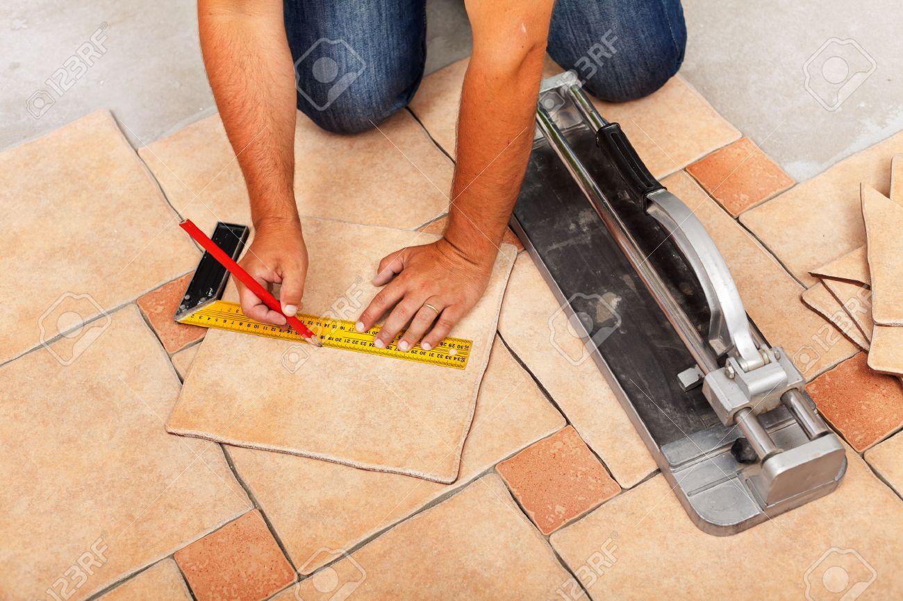 Installing ceramic floor tiles - measuring and cutting the pieces, closeup - 33270592