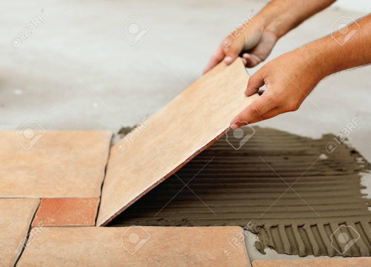 Installing ceramic floor tiles placing the tile into the adhesive installing ceramic floor tiles placing the tile into the adhesive material bedding closeup stock dailygadgetfo Images