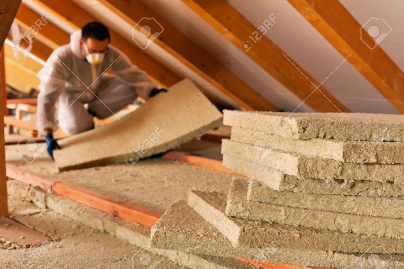 Man installing thermal insulation layer under the roof - using mineral wool panels - 34051671
