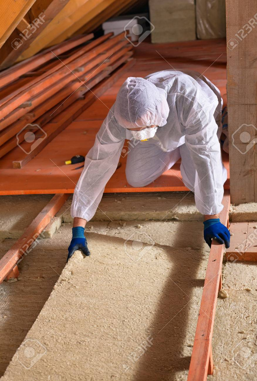 Man installing thermal insulation layer under the roof - using mineral wool panels - 34562122
