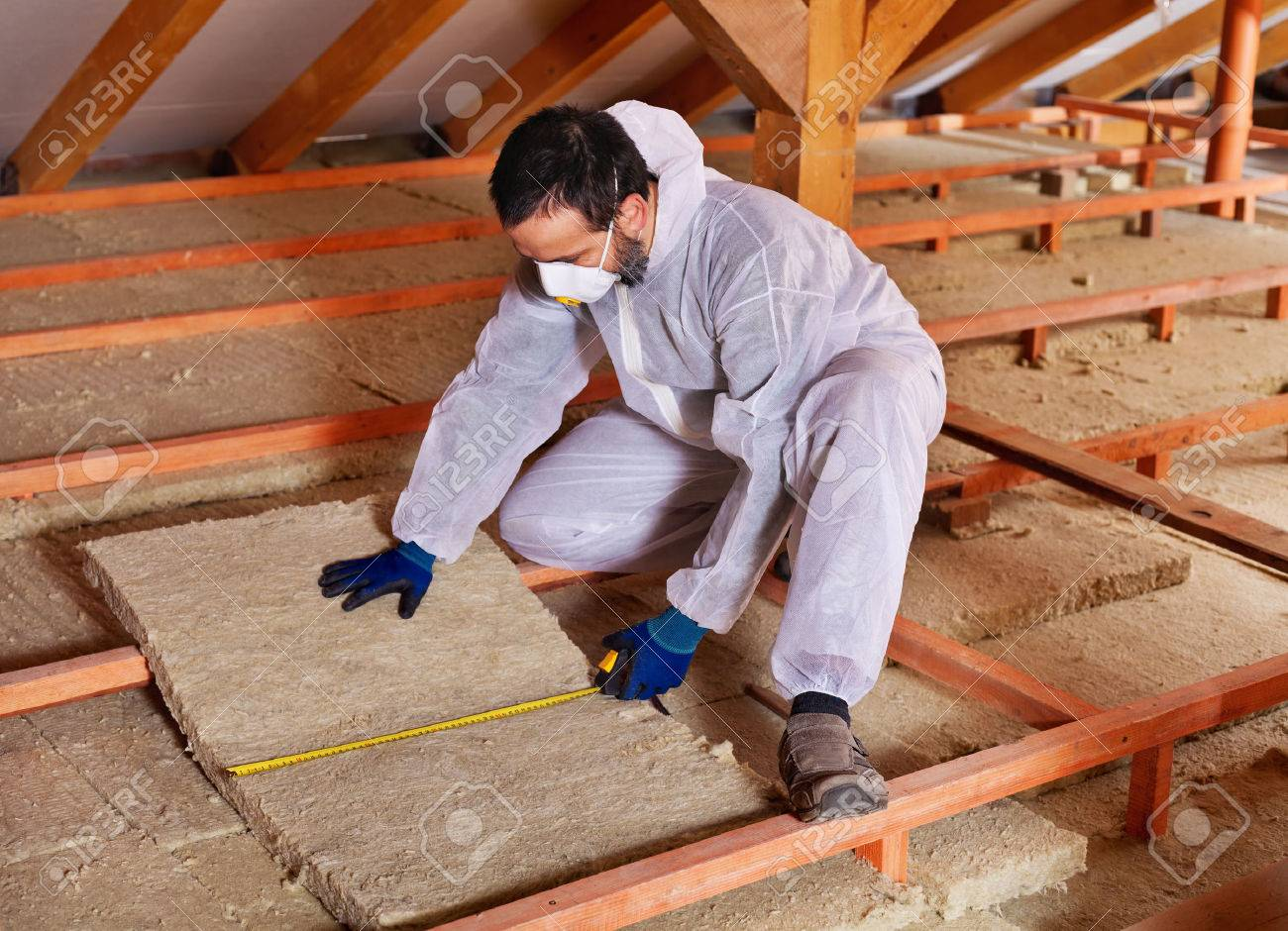Man laying thermal insulation layer under the roof - measuring a mineral wool panel - 35647543