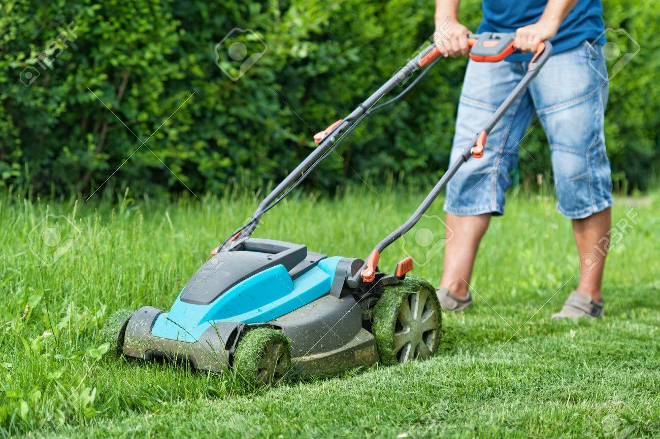 Man mowing the lawn with blue lawnmower in summertime - closeup - 54459014