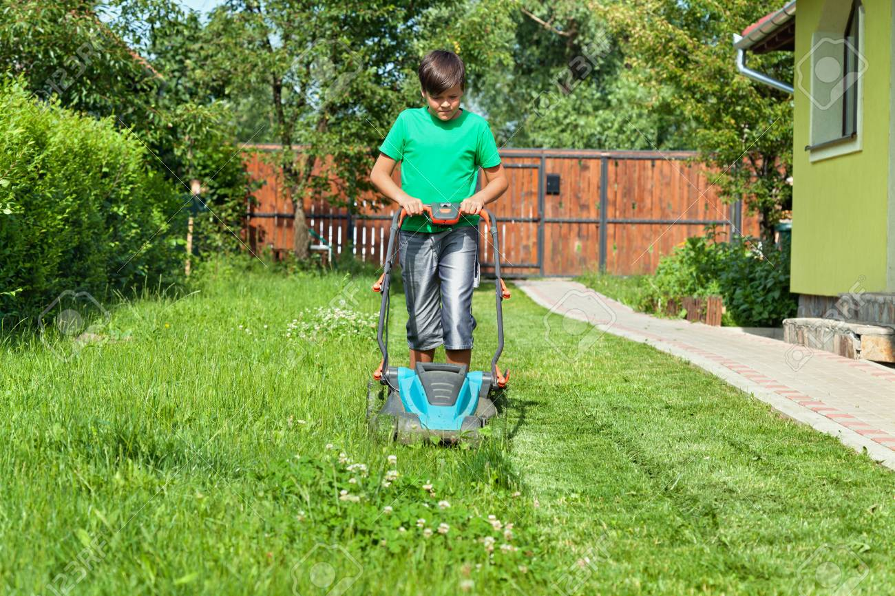 Boy cutting grass around the house in summertime - focusing on the operation - 54459021