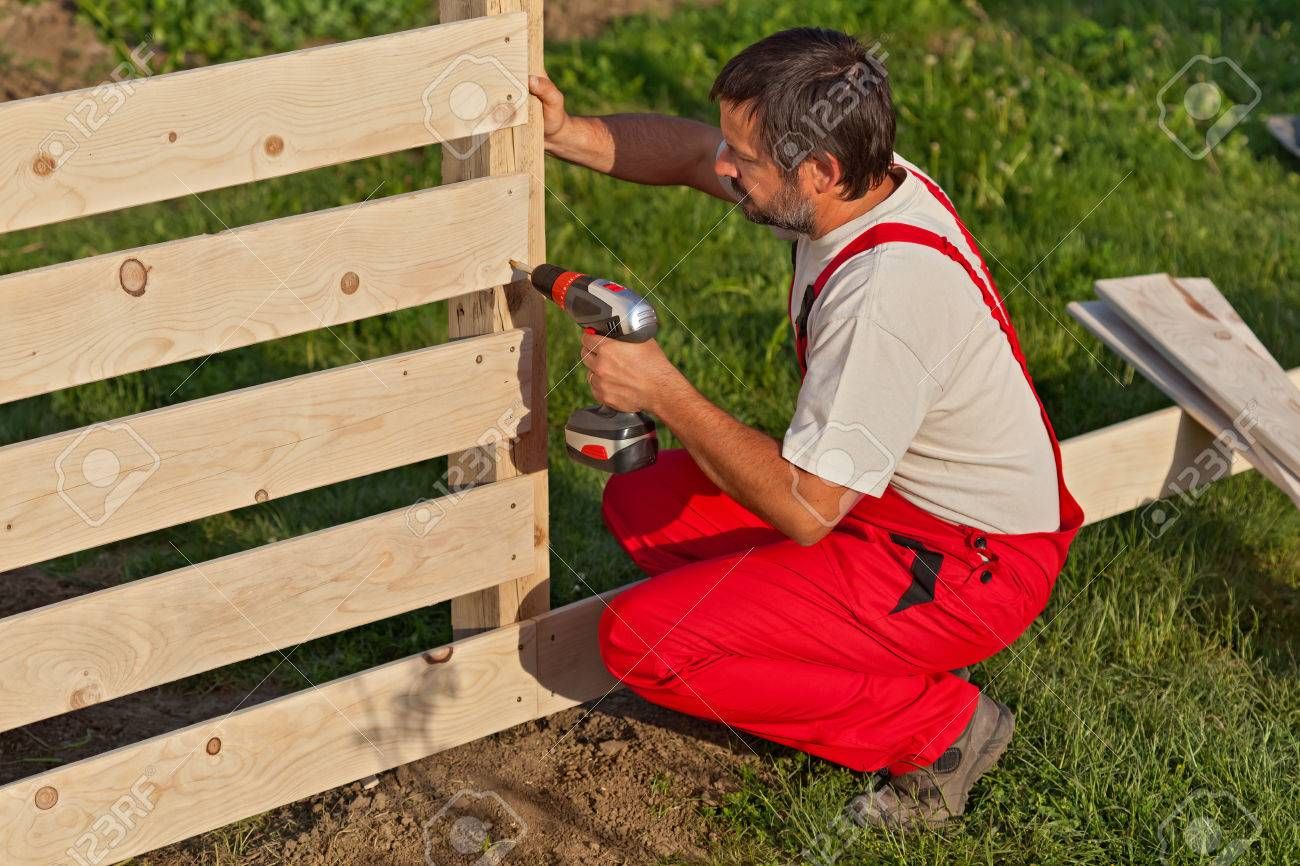 Man building a wooden fence - fastening the boards with screws - 55262324