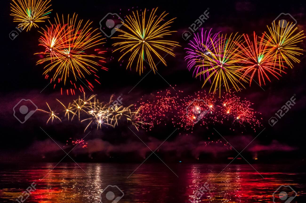Bright festive fireworks reflected in the river - 136398560