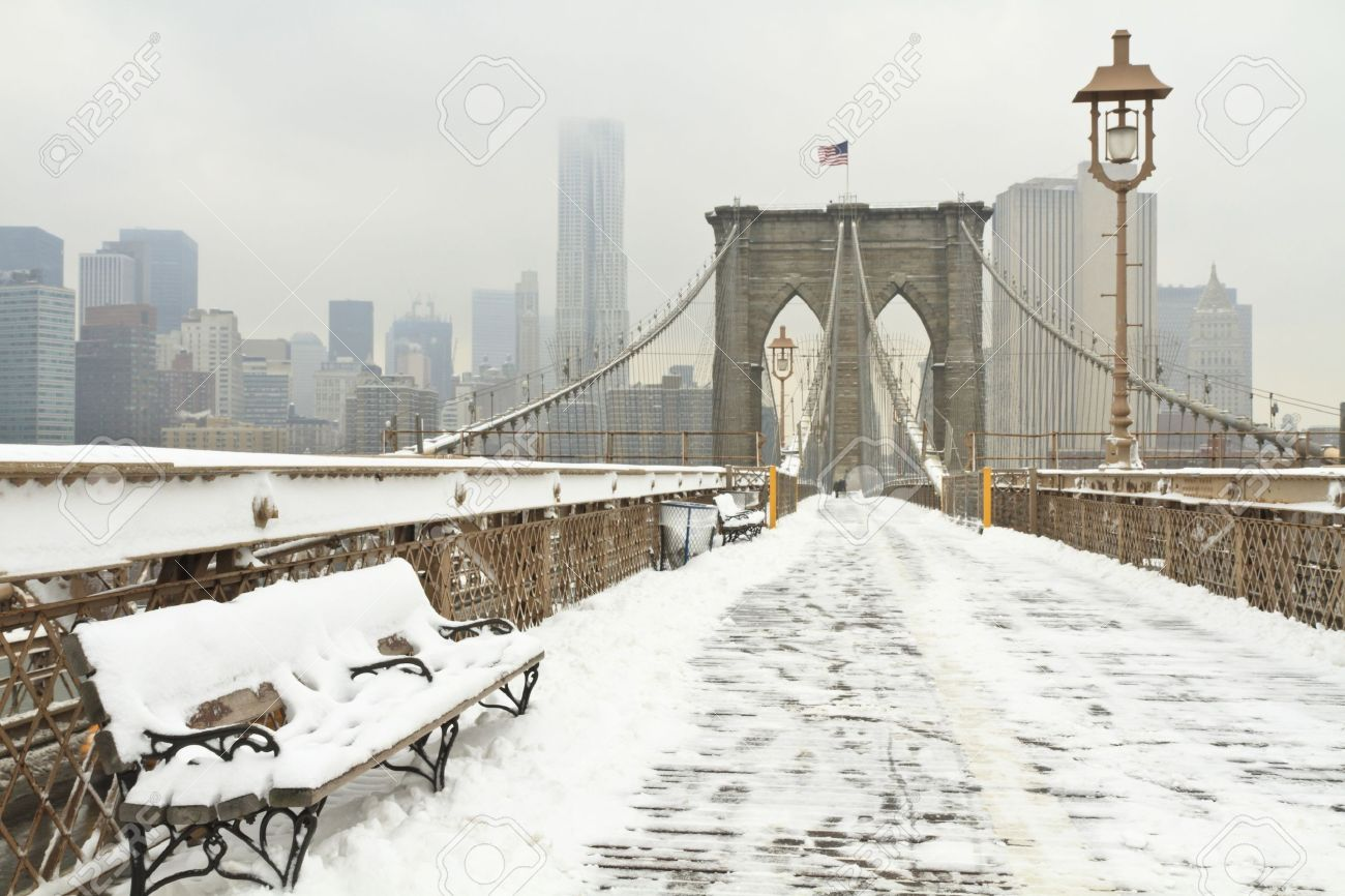 Horizontal photo of a bench on the Brooklyn Bridge during a snowstorm - 11545770