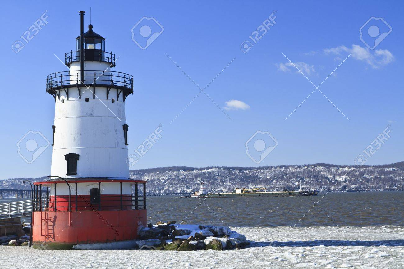 A barge head sup the icy Hudson River behind the Sleepy Hollow Lighthouse - 11545894