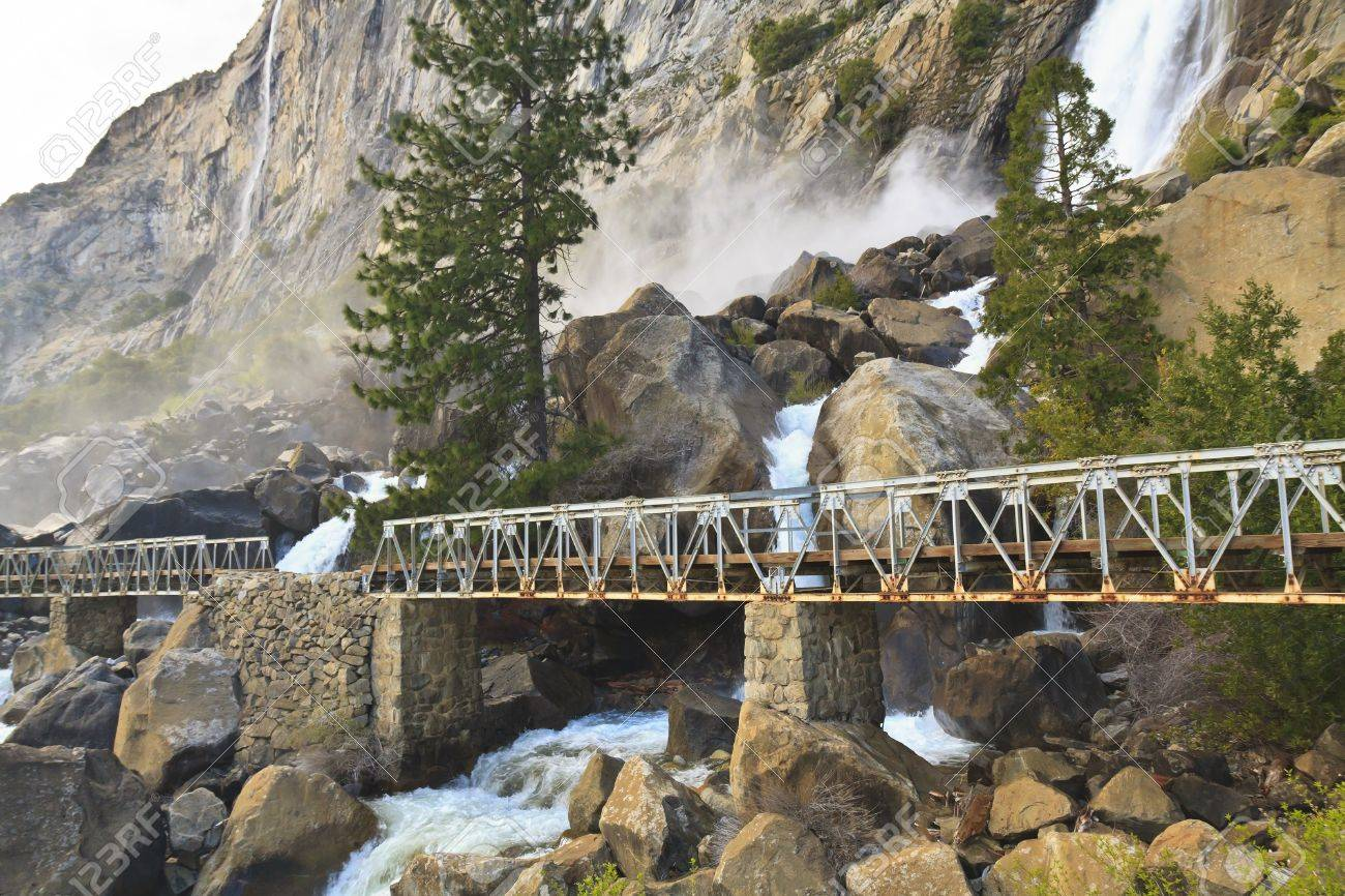 Misty Wapama Falls divides and spills under a footbridge and between boulders before falling into the Hetch Hetchy Reservoir in Yosemite National Park, California - 13438786