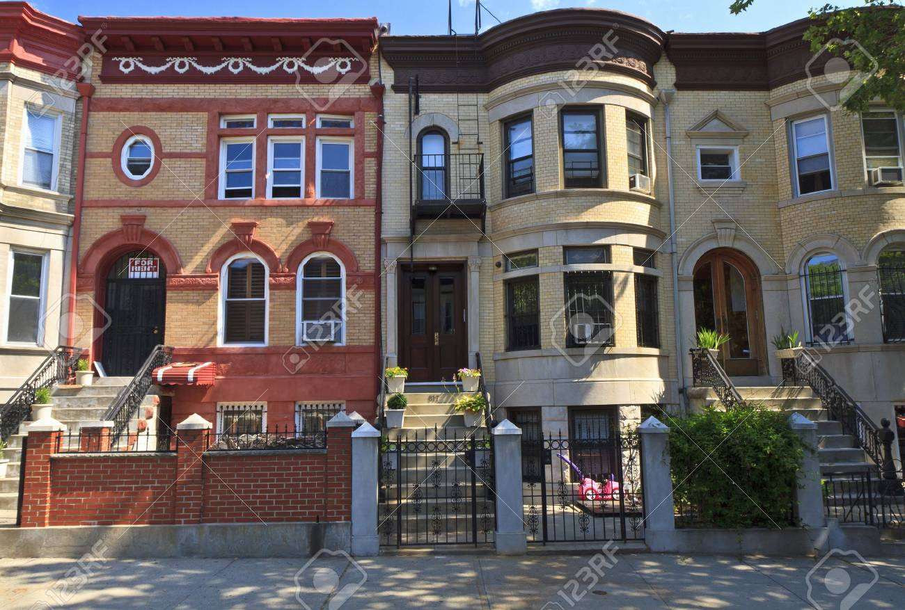 brick apartment building. A row of attached brick apartment buildings with stoops on Lincoln Place in  the Crown Heights Row Of Attached Brick Apartment Buildings With Stoops On