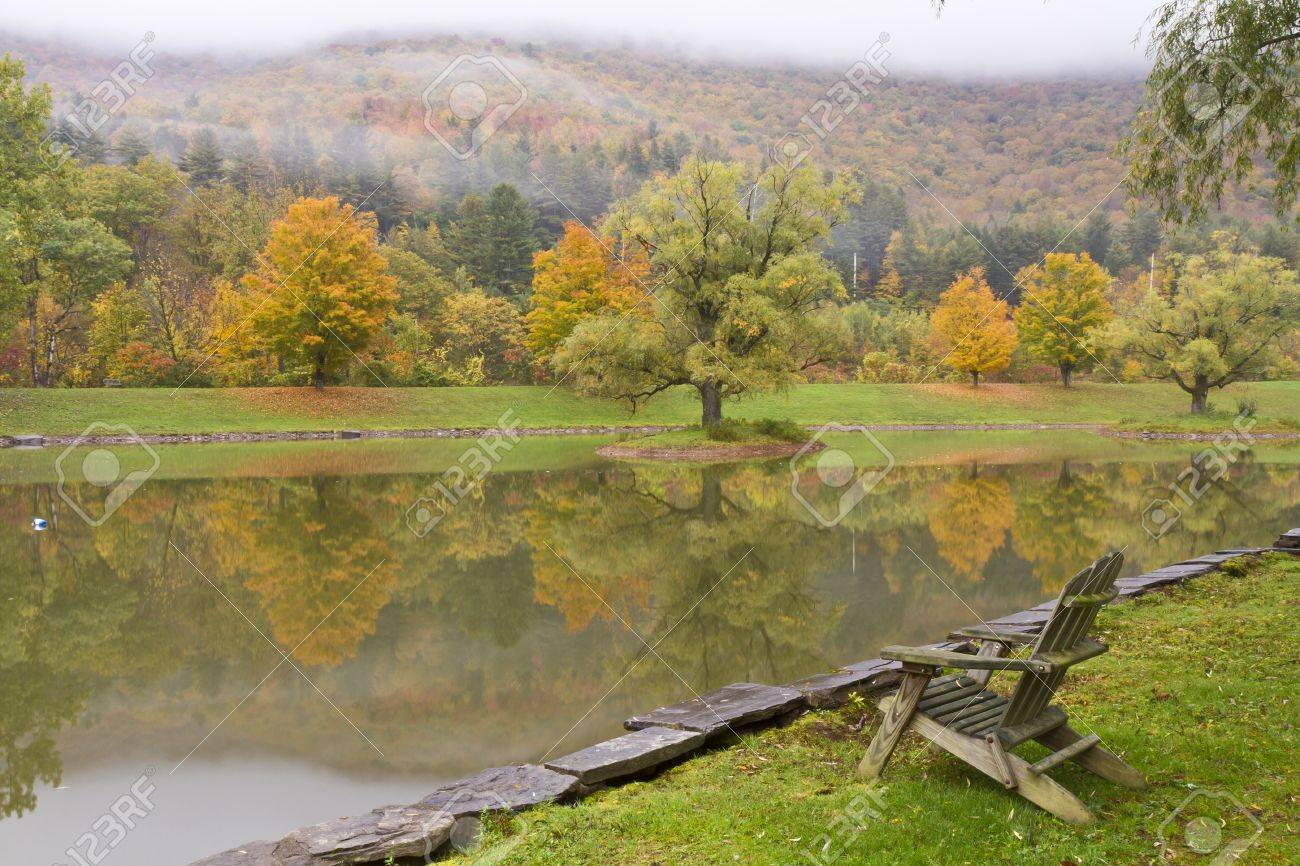 An Adirondack style wooden chair on the bank of a misty Autumn pond in the Catskills Mountains in Big Indian, NY - 20286346