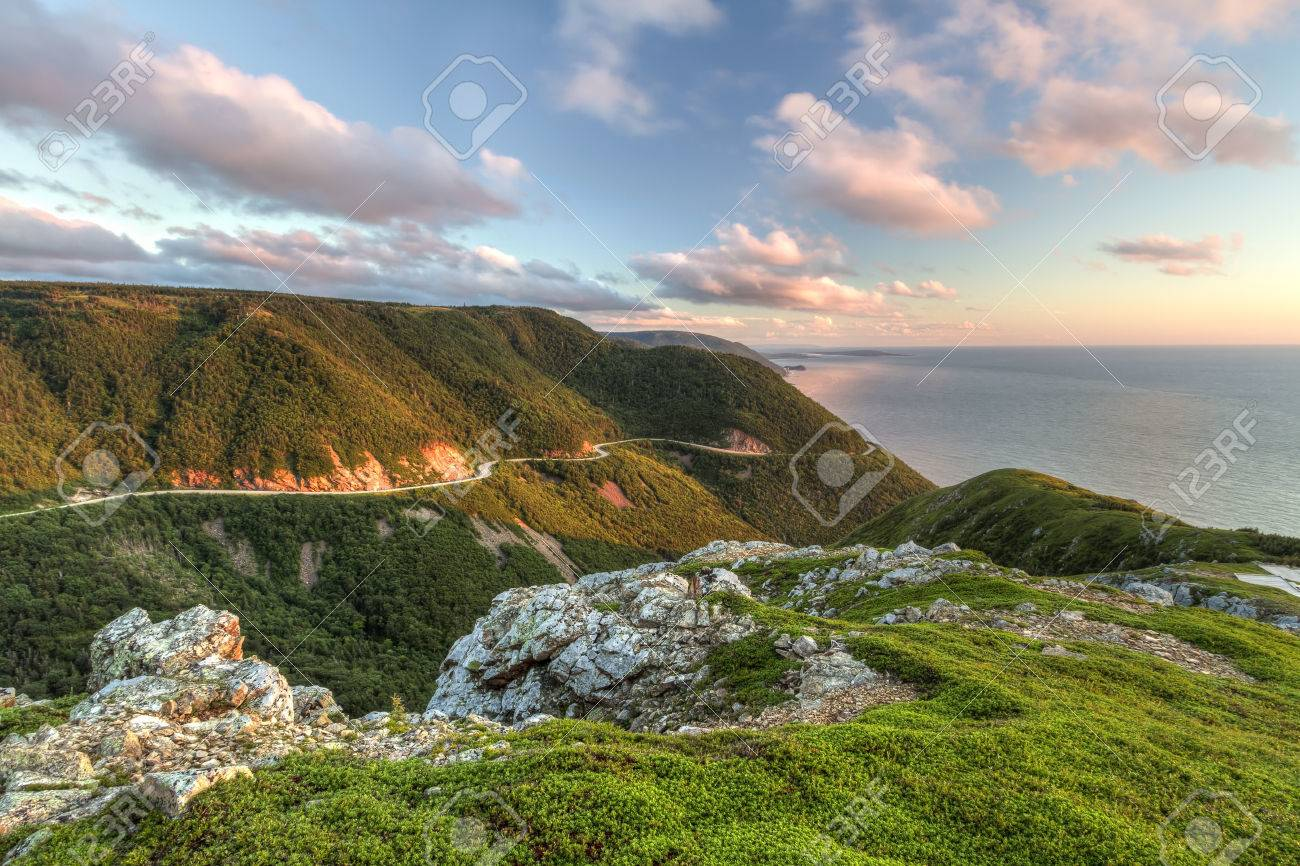 The winding Cabot Trail road seen from high above on the Skyline Trail at sunset in Cape Breton Highlands National Park, Nova Scotia - 24562916