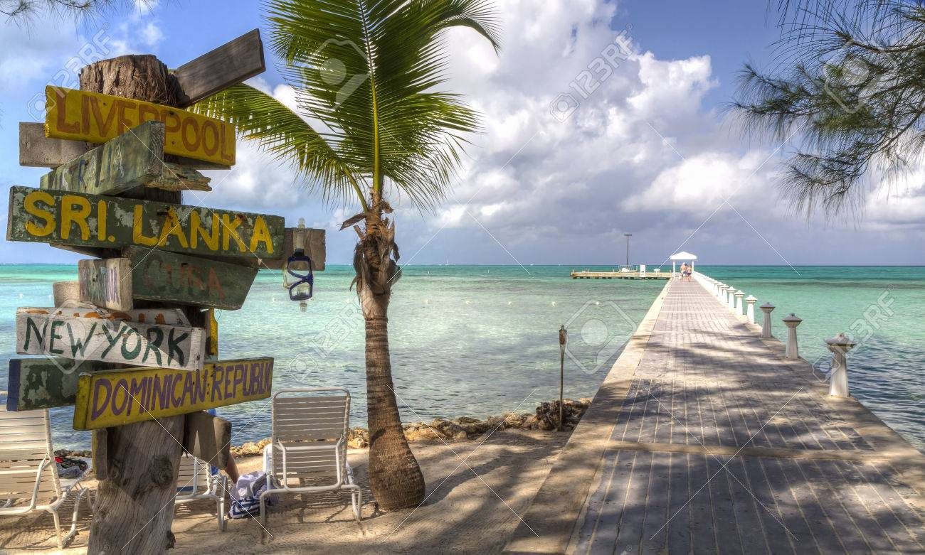 A signpost with various destinations next to the blue-green crystal clear waters off Rum Point dock on the north side of Grand Cayman, Cayman Islands, BWI - 25966634
