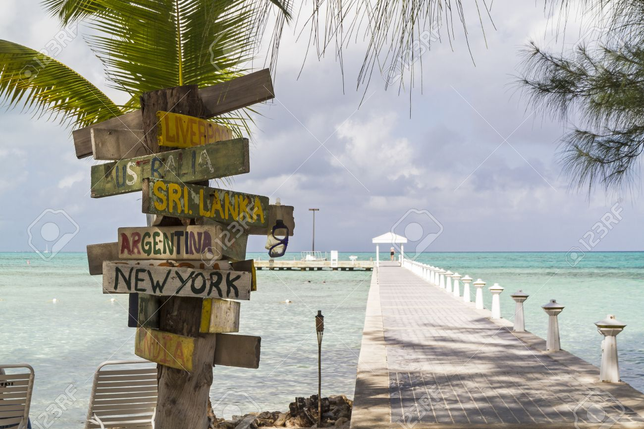 A signpost with various destinations next to the blue-green crystal clear waters off Rum Point dock on the north side of Grand Cayman, Cayman Islands, BWI - 25966674