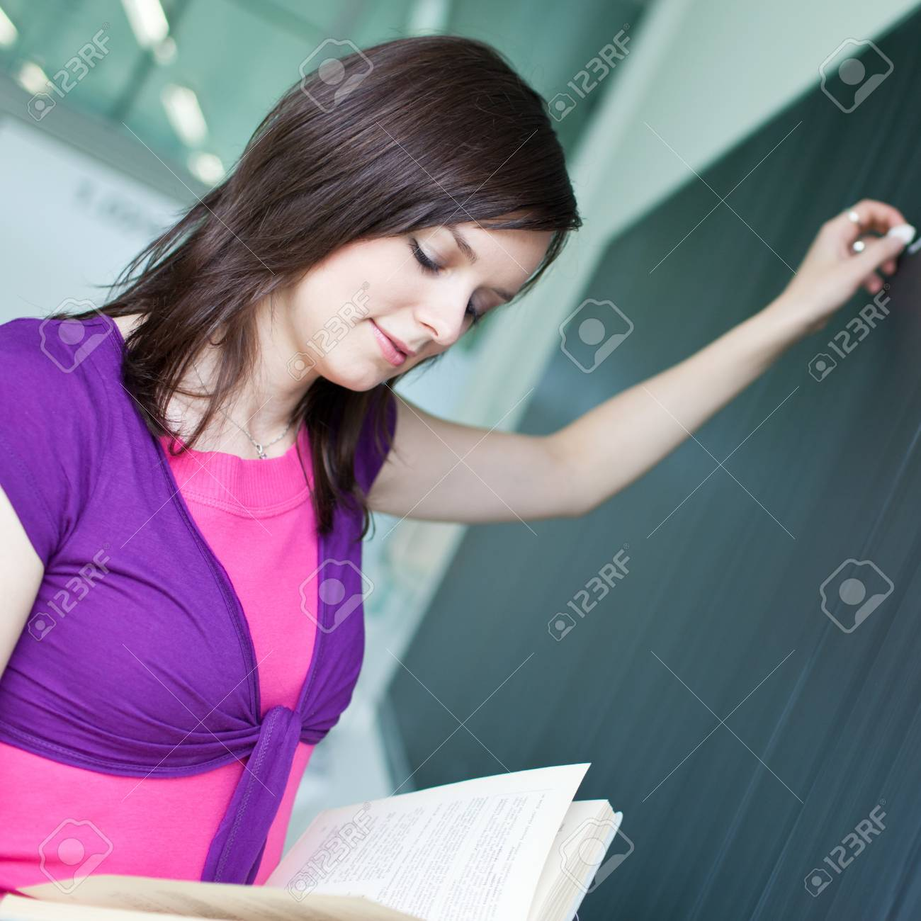 pretty young college student writing on the chalkboard/blackboard during a math class Stock Photo - 9697203