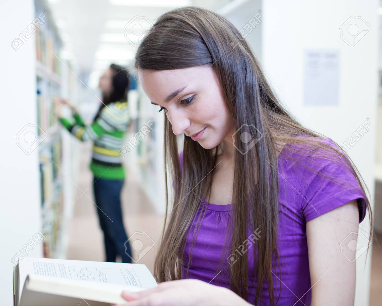 two pretty, young college students in a library (shallow DOF; color toned image) Stock Photo - 9792264