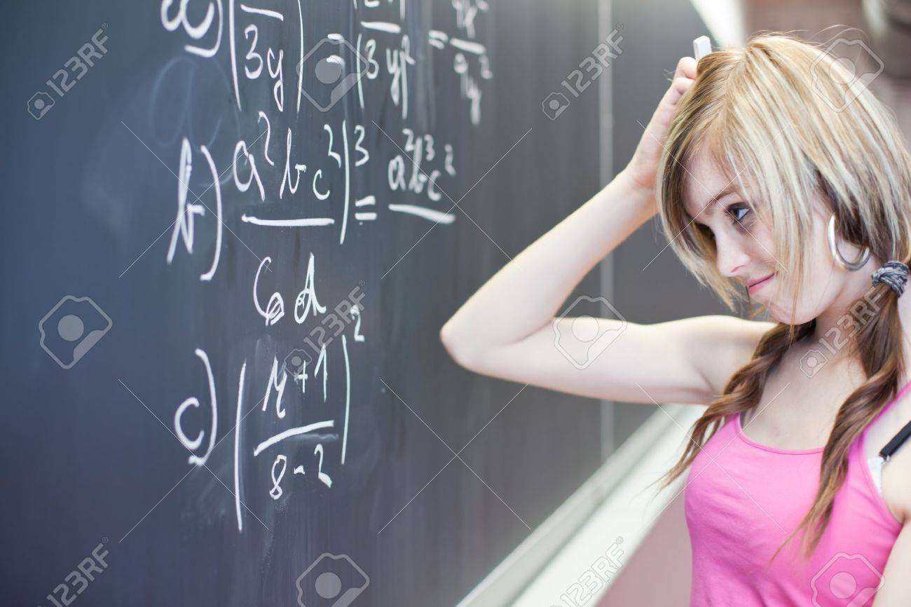pretty young college student writing on the chalkboard/blackboard during a math class (shallow DOF; color toned image) Stock Photo - 9798341
