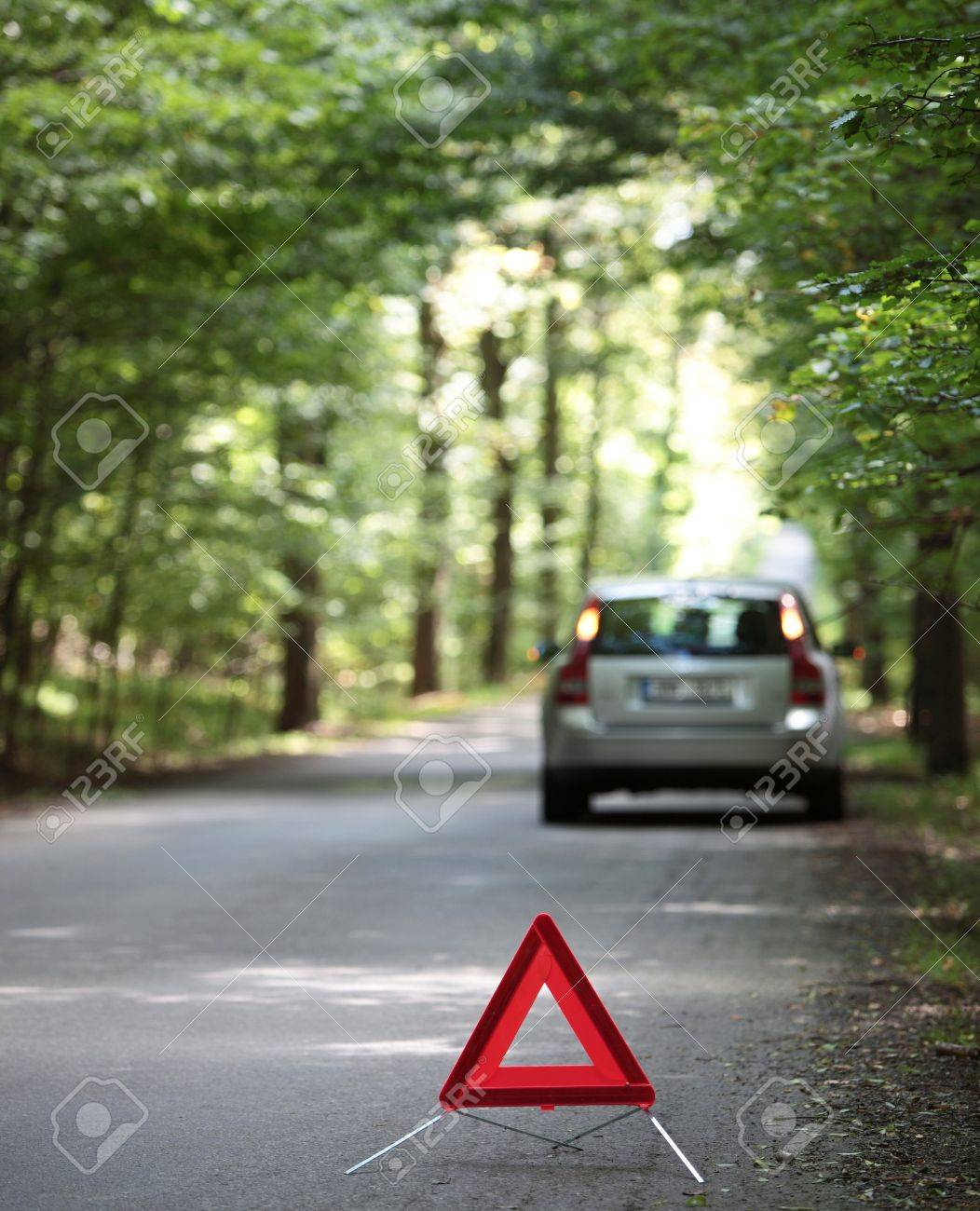 broken down car with warning triangle behind it waiting for assistance to arrive (shallow depth of field, the focus is on the triangle, the car is left out of focus) Stock Photo - 9817544