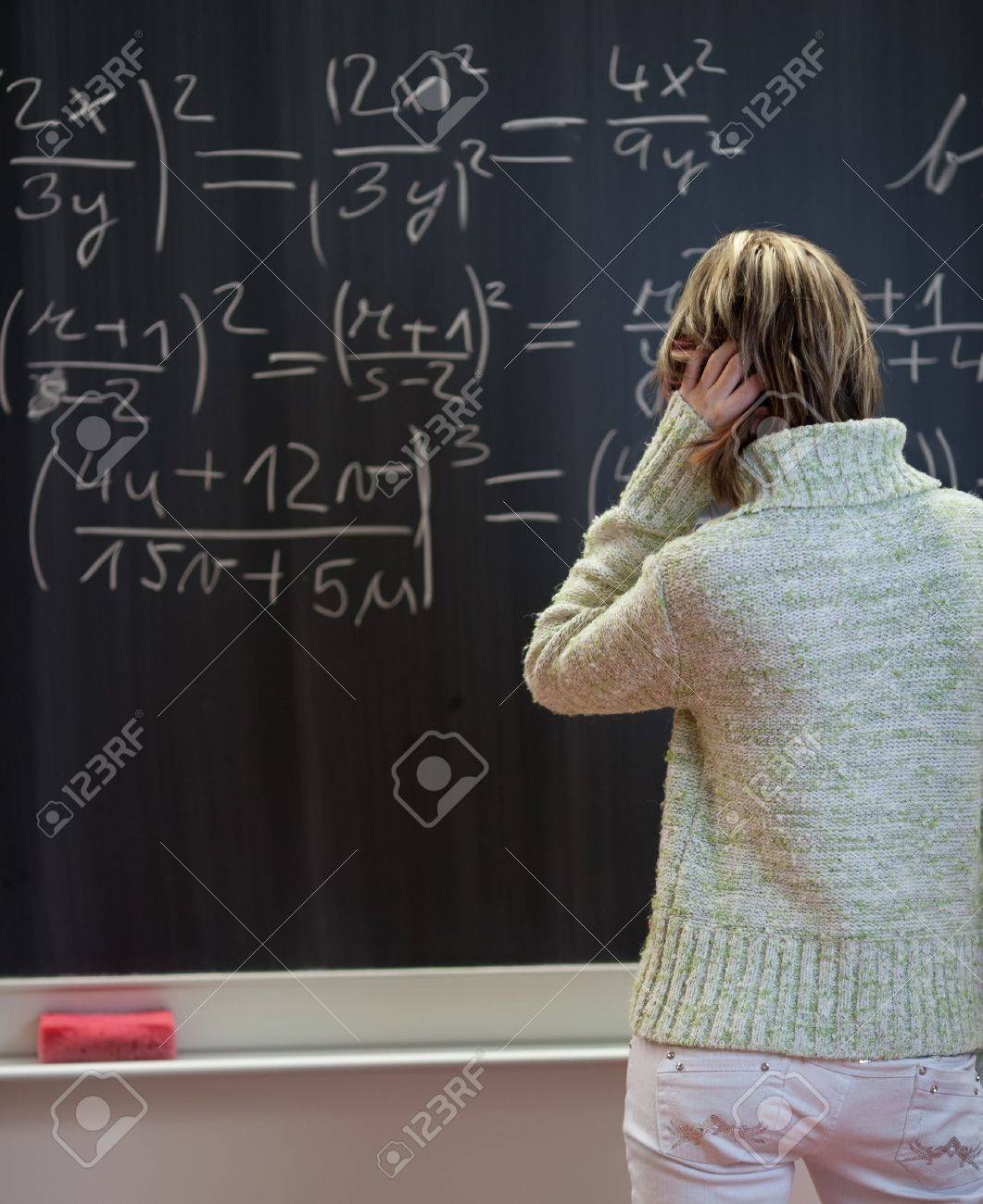 pretty college student standing in front of a chalkboard in a classroom and trying to find a solution to a math problem Stock Photo - 9804158