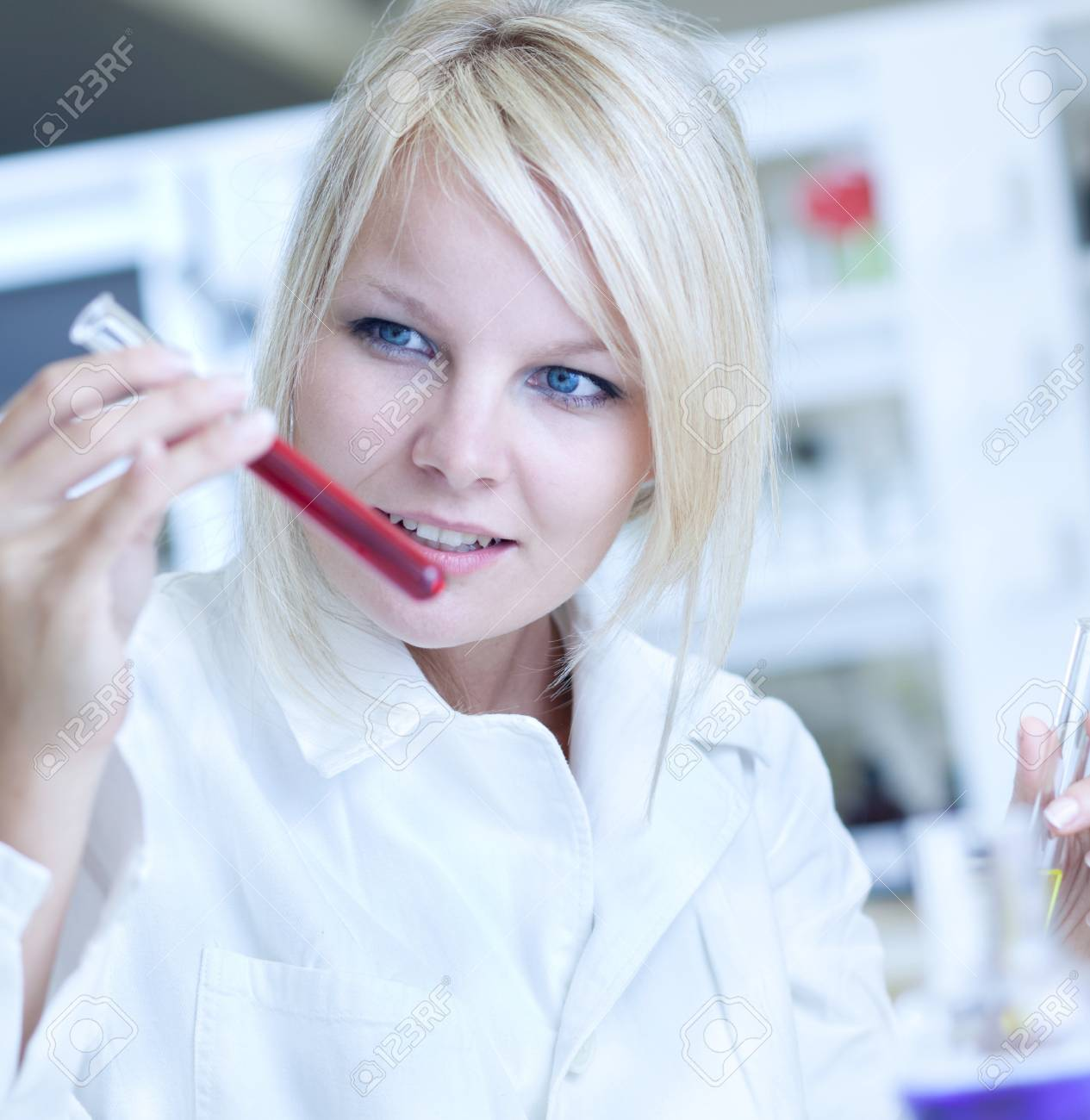 Closeup of a female researcher holding up a test tube and a retort and carrying out some experiments Stock Photo - 9793692