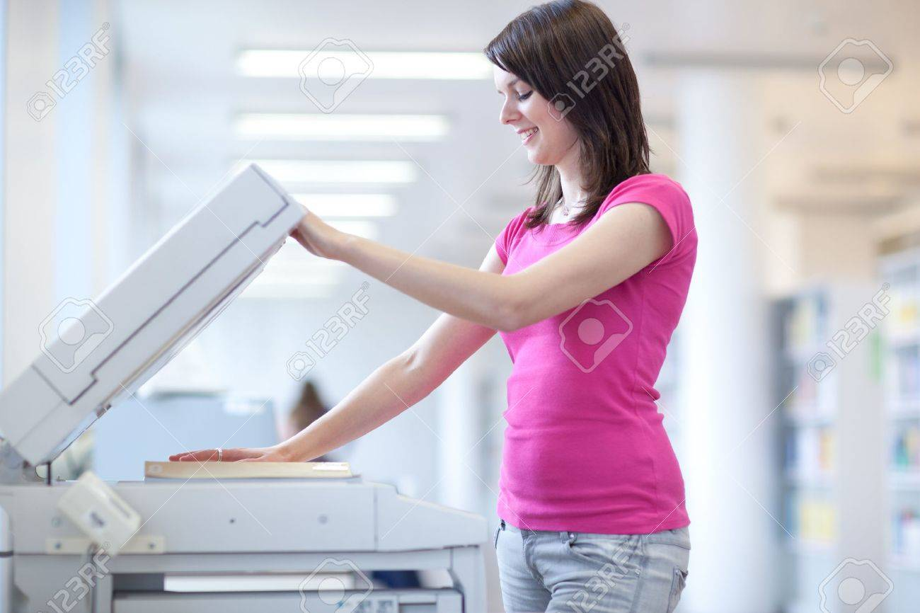 stock photo pretty young woman using a copy machine shallow dof color toned image - Color Copy Machine