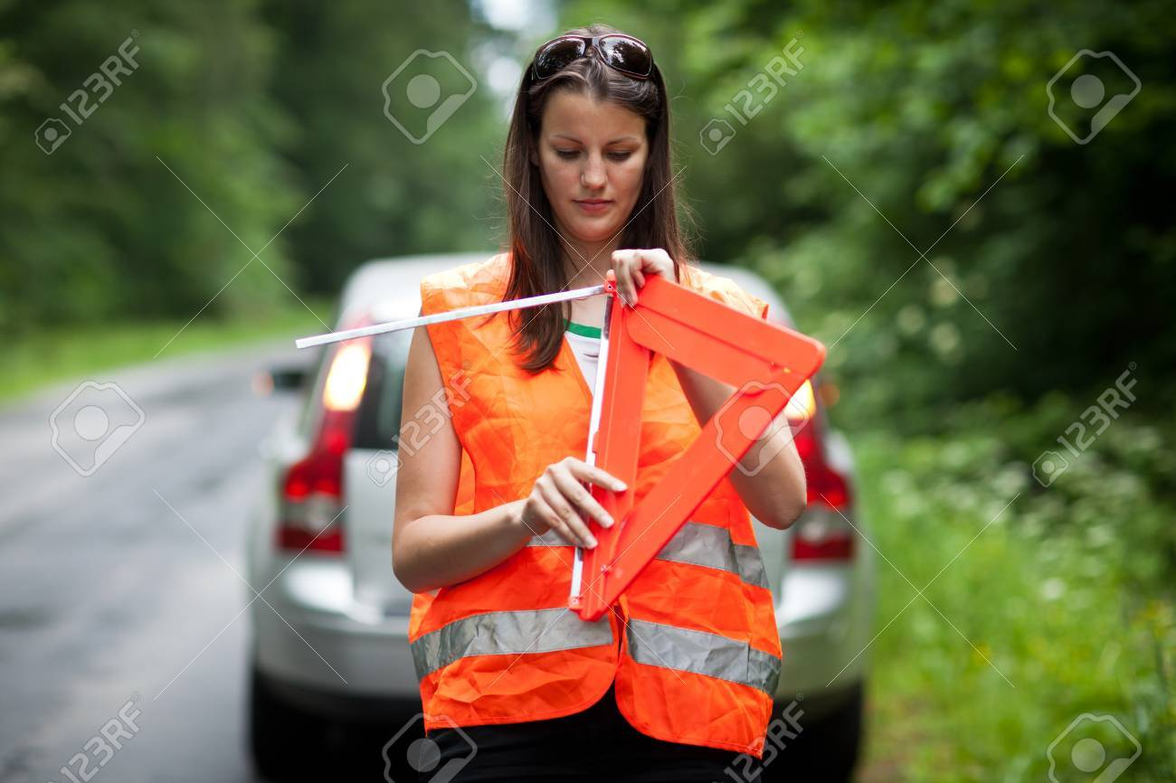 Young female driver wearing a high visibility vest/safety vest, putting in place the warning triangle after her car has broken down Stock Photo - 10410004
