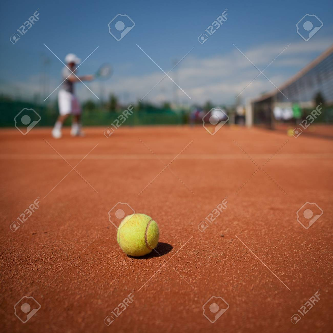 Tennis player in action on tennis court (selective focus, focus on ball in the foreground) Stock Photo - 10895256