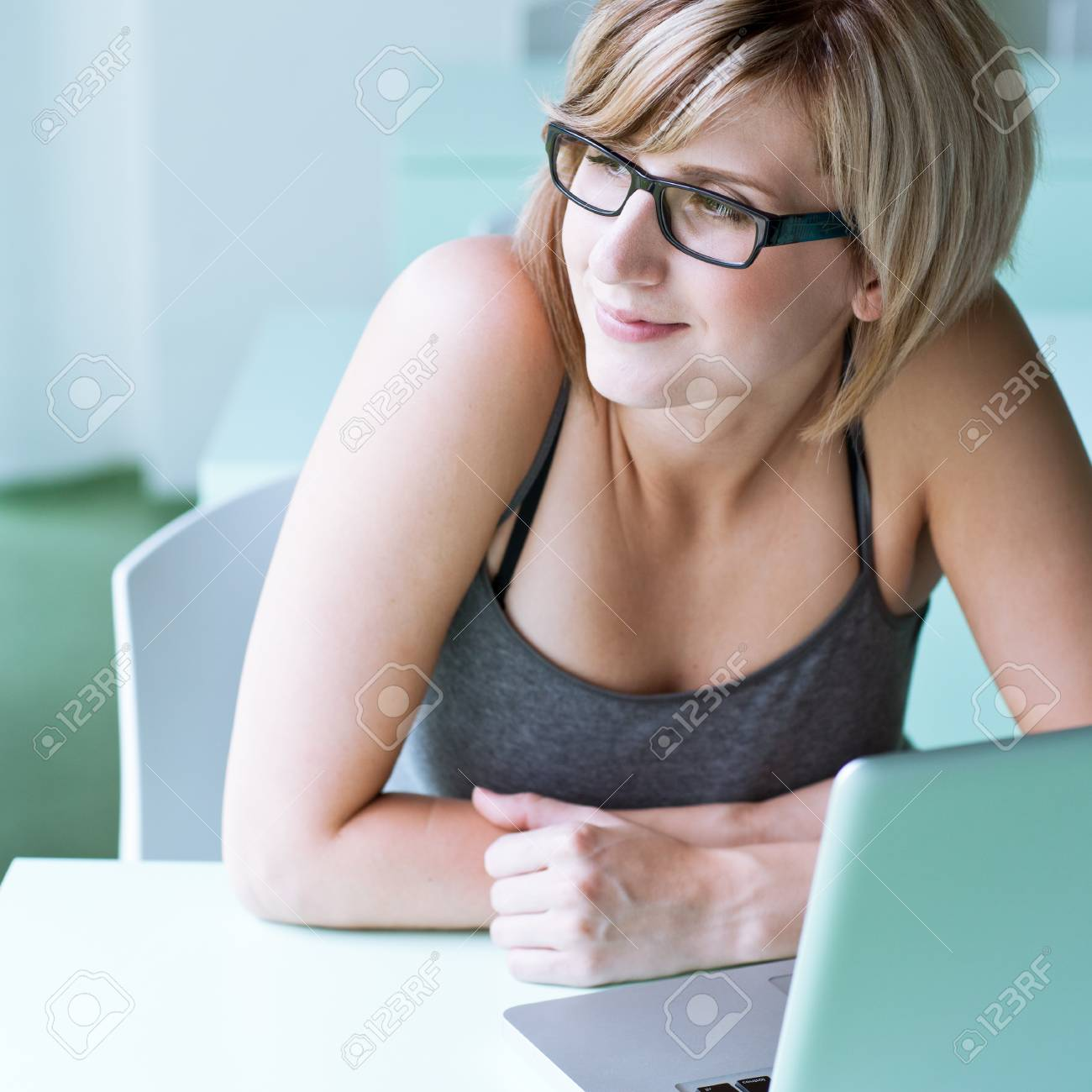 Portrait of a young woman pensively looking out of the window while sitting in front of her laptop Stock Photo - 10895283