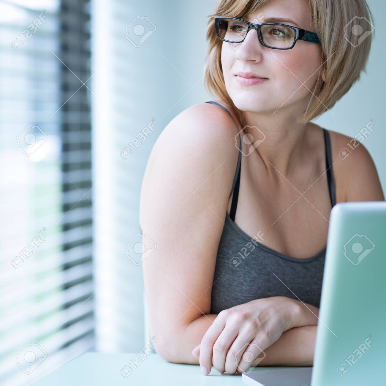 Portrait of a young woman pensively looking out of the window while sitting in front of her laptop Stock Photo - 10895210