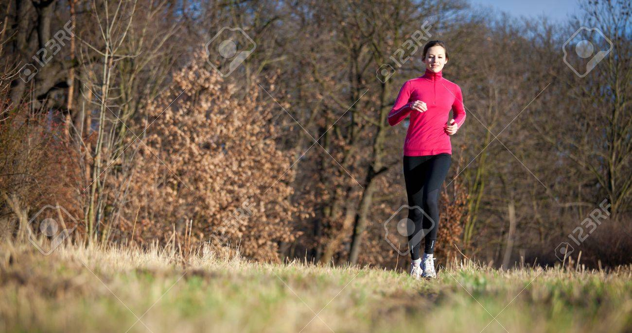 Young woman running outdoors on a lovely sunny winter/fall day (motion blurred image) Stock Photo - 11940514