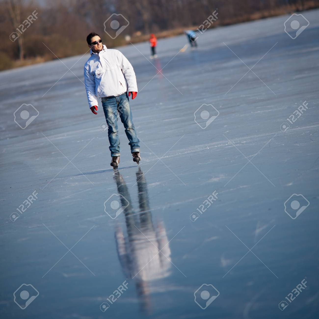 Handsome young man ice skating outdoors on a pond (color toned image; shallow DOF) Stock Photo - 12405450