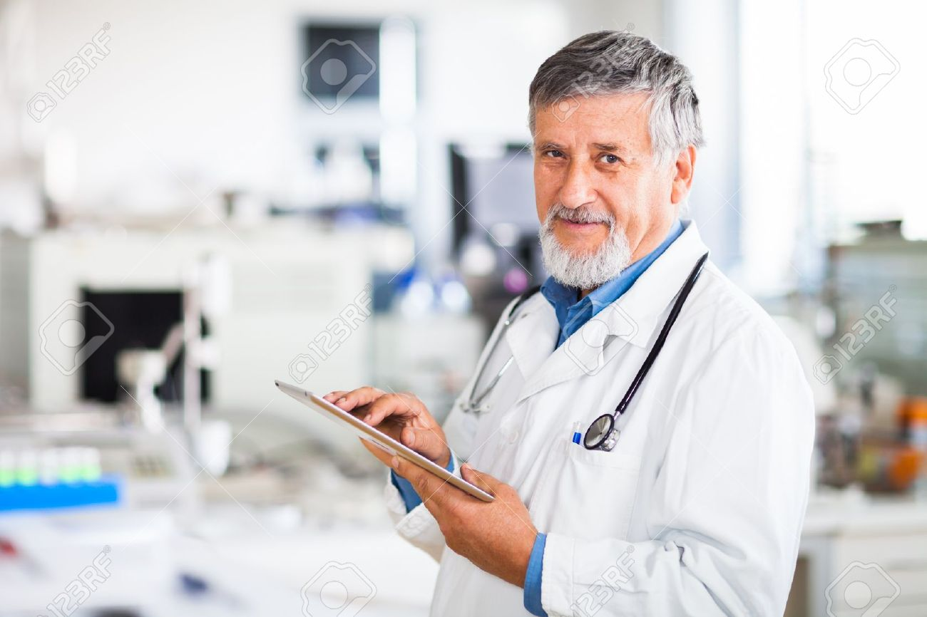 Senior doctor using his tablet computer at work  color toned image Stock Photo - 13531697
